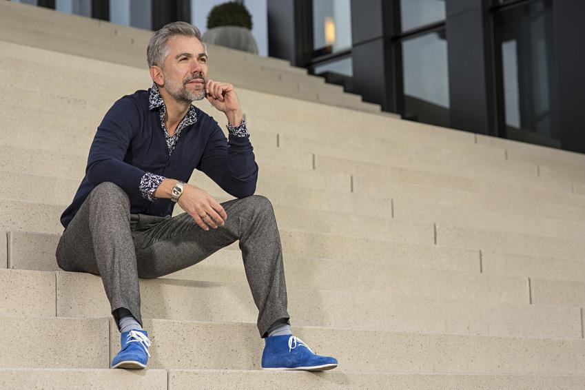 Mann sitzt nachdenklich auf einer Treppe